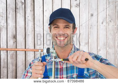 Portrait of happy plumber fixing pipe against digitally generated grey wooden planks