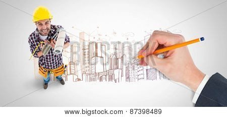 Hand writing with a pencil against large city buildings together