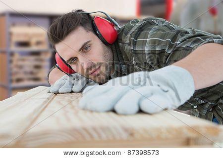Carpenter measuring wooden plank against workshop
