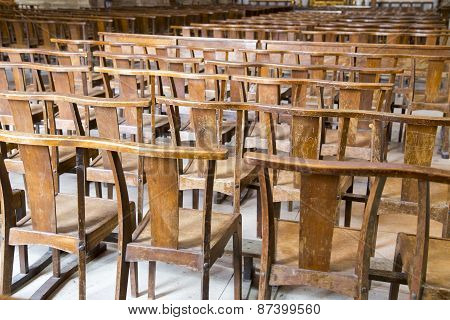 Rows Of Many Worn Wooden Chairs In A Church Illuminated Behind With Sun Light