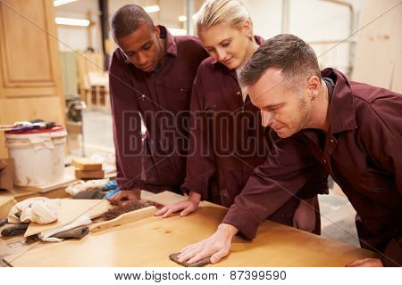 Carpenter With Apprentices Finishing Wood In Workshop