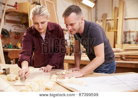 Carpenter With Female Apprentice Planing Wood In Workshop
