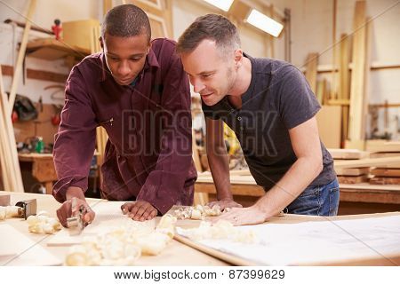 Carpenter With Apprentice Planing Wood In Workshop