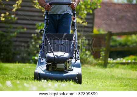 Close Up Of Man Working In Garden Cutting Grass With Mower