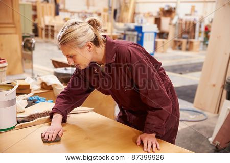 Female Apprentice Finishing Wood In Carpentry Workshop
