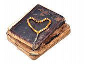 picture of prayer beads  - Heart shape beads on old book on a white background - JPG