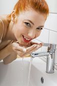pic of wash-basin  - Close up Happy Young Woman Washing her Face While Looking at the Camera for a Moment - JPG