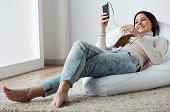 image of model home  - Portrait of beautiful young woman listening to music with mobile phone at home - JPG