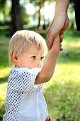 image of disobedient  - Sad Child hold the Parent Hand in the Summer Park - JPG