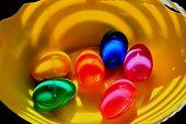 pic of boy girl shadow  - Colorful Easter eggs in various bright colors filled with candy and sunlight and shadows creating an abstract design on the eggs and a vary bright yellow bowl - JPG