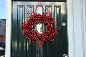 stock photo of christmas wreath  - Berry christmas wreath with decorations on a door - JPG