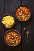 stock photo of sweet-corn  - Overhead shot of two rustic bowls of vegetarian chili dish made with kidney bean carrot zucchini bell pepper sweet corn tomato onion garlic with tortilla chips on the side photographed on dark wood with natural light - JPG