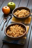 stock photo of crisps  - Two rustic bowls of baked apple crumble or crisp on kitchen towel wooden spoons and fresh apples on the side photographed on dark wood with natural light  - JPG