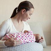 picture of breast-milk  - Happy mother breast feeding her newborn in room indoor - JPG