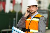 picture of supervision  - closeup portrait of young handsome architect supervising a construction using cell phone wearing helmet - JPG
