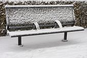 image of scrape  - Bench in snowfall. The left armrest is showing fingerprints scraping some snow.