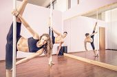 stock photo of pole dancer  - Couple dancing at pole in a fitness studio - Ballet dancers working out - Pole dancers looking at camera and stretching legs