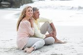 picture of couple sitting beach  - Happy couple sitting on the sand at the beach - JPG