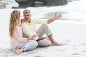 image of couple sitting beach  - Happy couple sitting on the sand at the beach - JPG