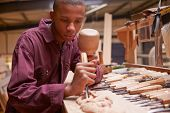 stock photo of chisel  - Apprentice Using Chisel To Carve Wood In Workshop - JPG