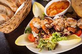 foto of endive  - Grilled prawns with a green leafy lettuce and endive salad and a jacket potato topped with sour cream served on a white plate close up high angle view on white - JPG