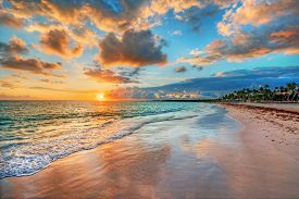 stock photo of inlet  - Bright and dynamic sea beach sunrise with bright blue skies and colorful clouds - JPG
