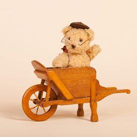 image of hand-barrow  - Hand made stuffed funny bear sitting in vintage wheel barrow - JPG