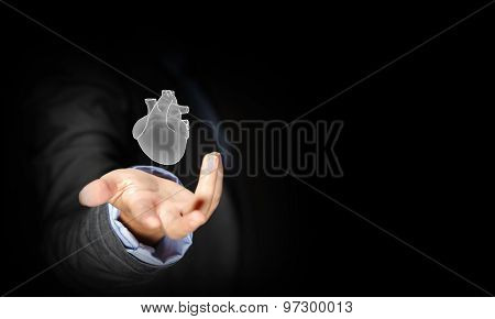 Close up of businessman holding human heart in palm