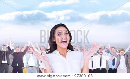 Surprised brunette with hands up against balcony overlooking city