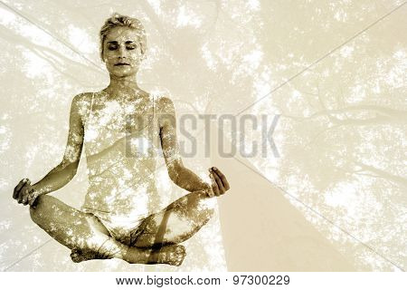 Toned young woman sitting in lotus pose with eyes closed against low angle view of tall trees