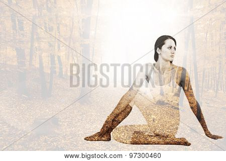Fit woman doing the half spinal twist pose in fitness studio against autumnal forest