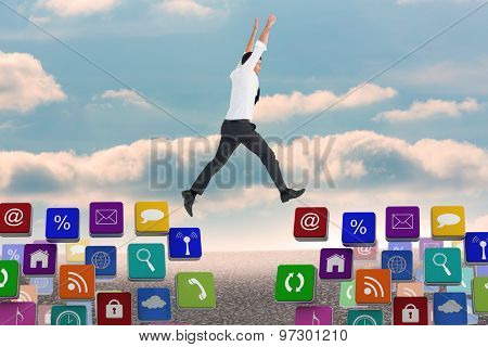 Cheering businessman against desert landscape with blue sky