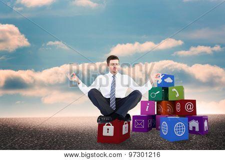 Businessman meditating in lotus pose against desert landscape with blue sky