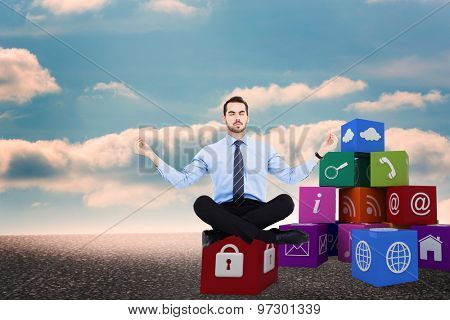 Calm businessman sitting in lotus pose against desert landscape with blue sky