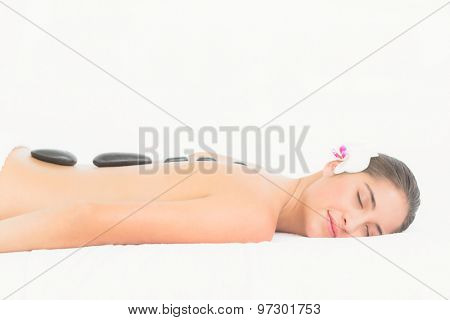 Portrait of a pretty woman enjoying a hot stone massage at the health spa