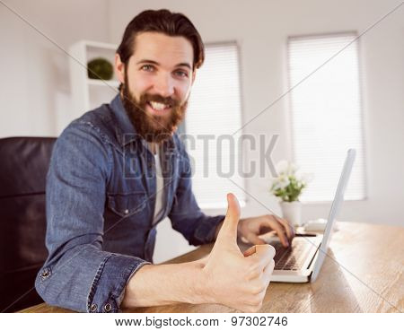 Hipster businessman showing thumbs up to camera in his office