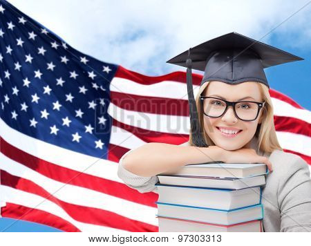 education, high school, knowledge and people concept - picture of happy student girl or woman in trencher cap with stack of books over american flag background