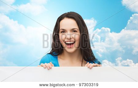 advertisement, sale and people concept - smiling young girl with blank white board over blue sky with clouds background