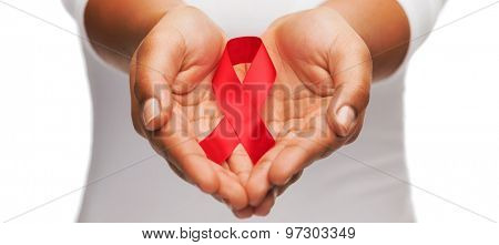 healthcare and medicine concept - female hands holding red AIDS awareness ribbon