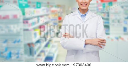 medicine, pharmacy, people, health care and pharmacology concept - happy young woman pharmacist over drugstore background