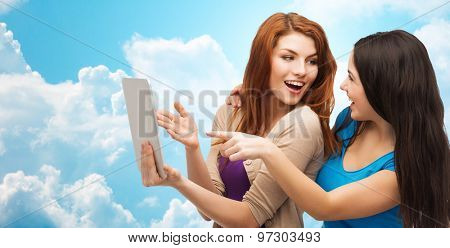 technology, friendship and people concept - two smiling teenage girls or young women pointing finger at tablet pc computer over blue sky with clouds background