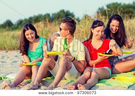 friendship, happiness, summer vacation, holidays and people concept - group of smiling friends having picnic on beach