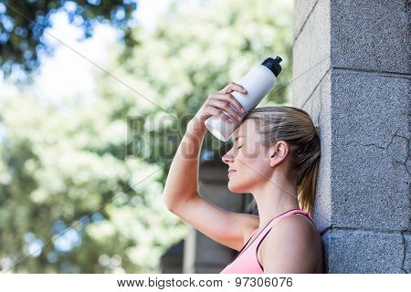 A beautiful woman holding a bottle of water on a sunny day