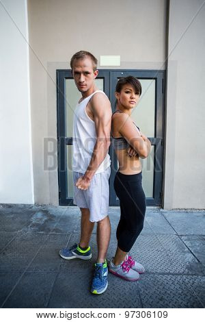Portrait of extreme athletes standing back to back and looking at camera in front of a building