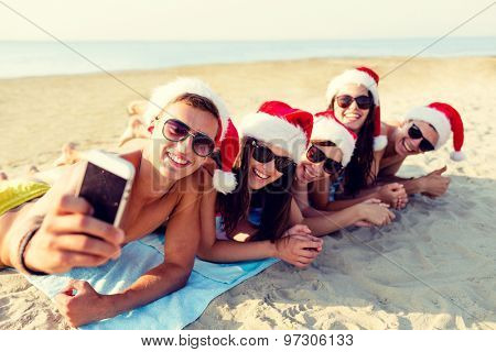 friendship, summer vacation, holidays, technology and people concept - group of friends in santa helper hats taking selfie with smartphone on beach