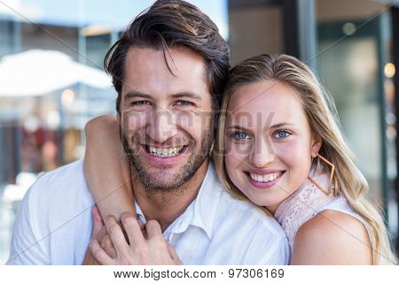 Portrait of smiling woman putting arm around her boyfriend at shopping mall