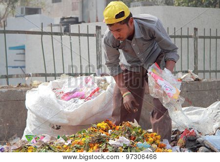 man is looking for something in pile of litter
