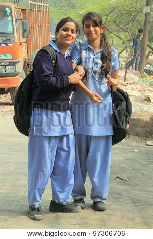 two girls in school clothes are smiling to someone