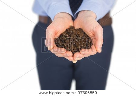 Businessman showing coffee beans on white background