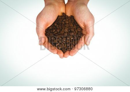 Hands showing coffee beans on a white background